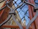 Zrcadlící se jižní věž baziliky Nanebevzetí Panny Marie a svatého Cyrila a Metoděje za mřížemi okna Stojanova gymnázia.